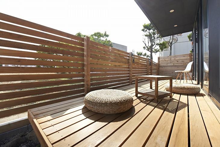 目隠しのフェンスや日差し除けをつけると安心。ウッドデッキの上の小物類もデッキの色とトーンを合わせれば部屋の窓から見える景色もすっきり