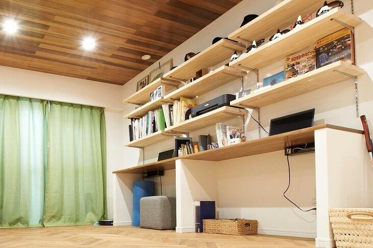 リビングの造作デスクで、上には収納空間。壁付にすると、リビングに対し背中を向けることになるので、視野も制限され、作業に集中しやすい