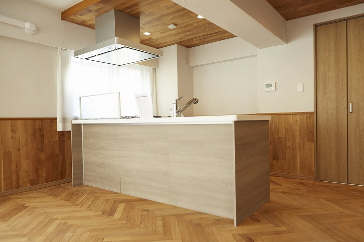LDKのキッチン部分のみ無垢材天井にした例。圧迫感が軽減される