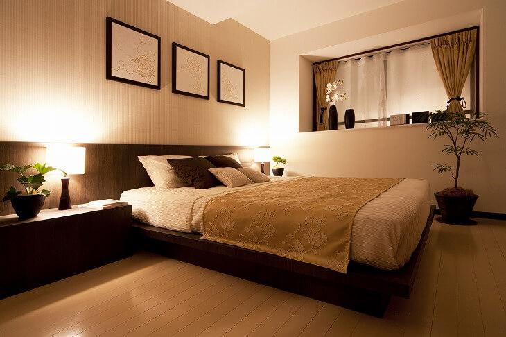 寝室には寒色と暖色の組み合わせが最適。壁紙をナチュラルなベージュ、ベッドやサイドテーブルをブラウンで統一すると落ち着いた空間に