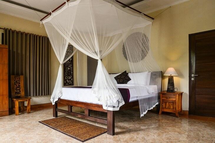 ダークブラウンの木製フレームのベッドに天蓋をかけて、クッションにエキゾチックな柄を取り入れればまるでホテル