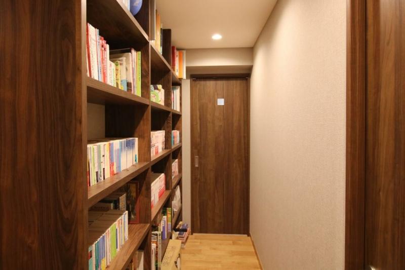 廊下の壁面を活用した本棚は、ドアの色と合わせた無垢材で統一感を演出