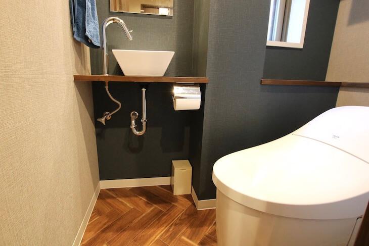 落ち着いた青色のアクセントクロスとヘリンボーンの床でトイレもおしゃれな印象に